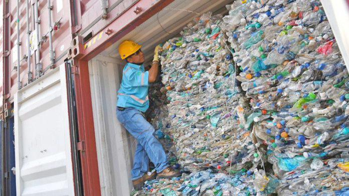 An officer stands inside a container full with plastic waste at Tanjung Priok port in Jakarta, Indonesia, September 18, 2019